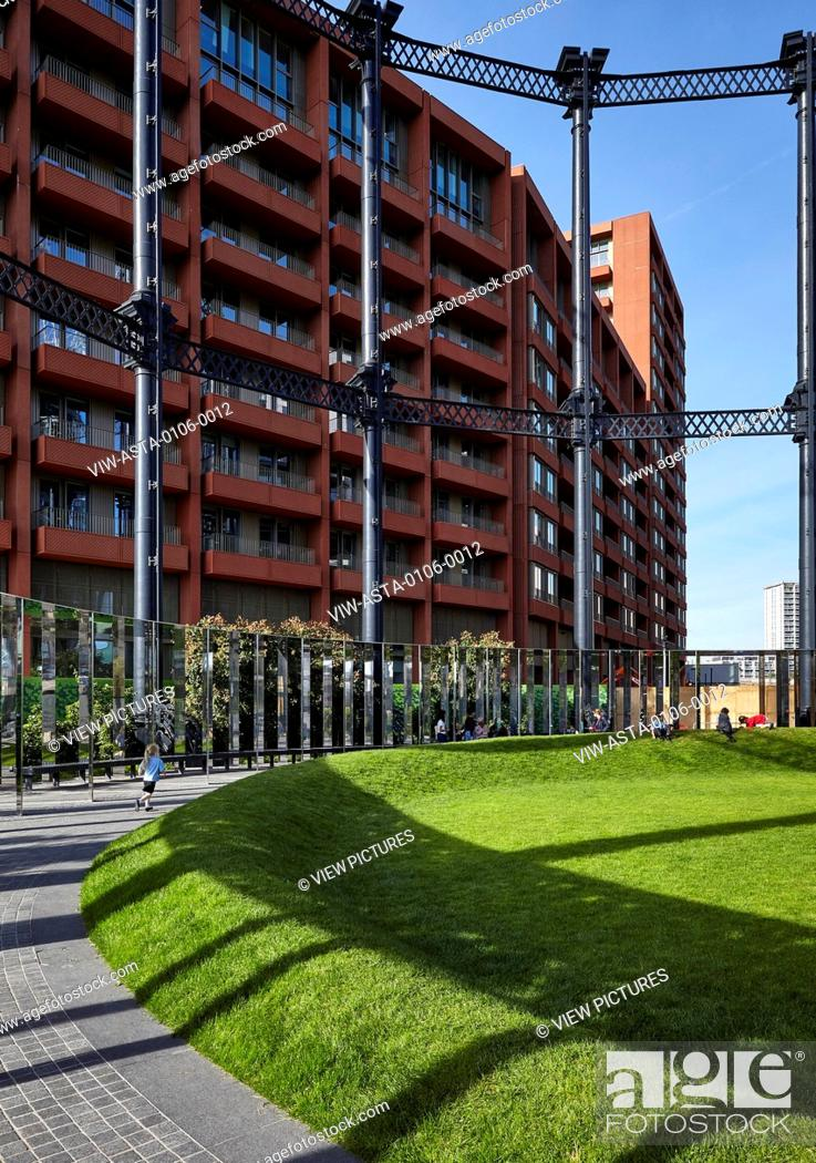 Children playing on the green space inside the gas holders