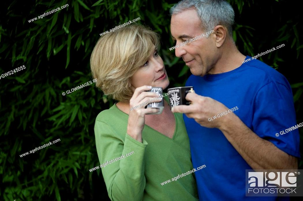 Stock Photo: Close-up of a senior man with a mature woman holding tea cups and looking at each other.