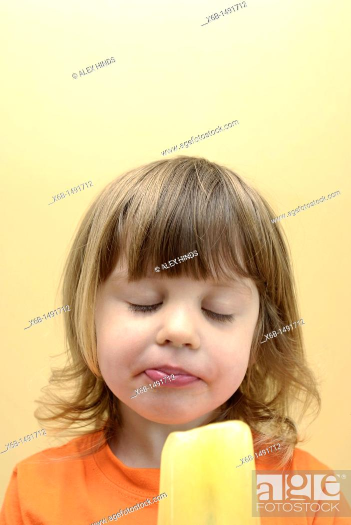 Stock Photo: Young girl eating a frozen ice pop.
