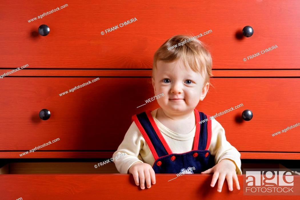 Stock Photo: Baby boy playing inside cupboard drawer.