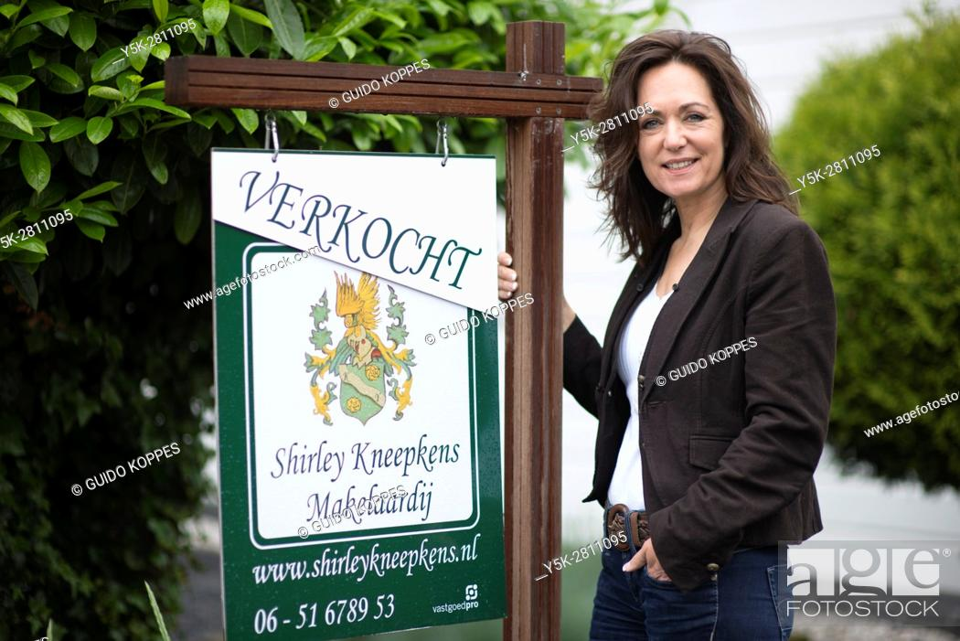 Stock Photo: Tilburg, Netherlands. Portrait of a female real estate agent, in front of a residential house just being sold.