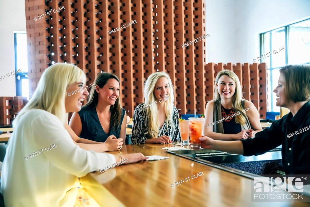 Stock Photo: Caucasian bartender serving cocktail to women.