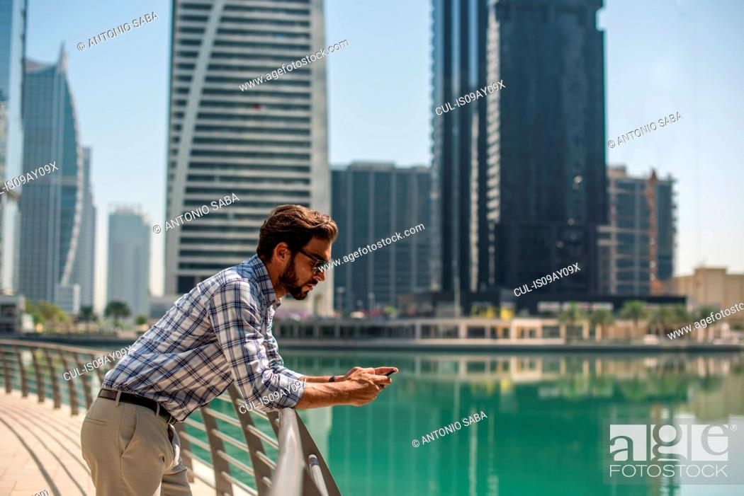 Stock Photo: Young man leaning against waterfront railings reading smartphone texts, Dubai, United Arab Emirates.