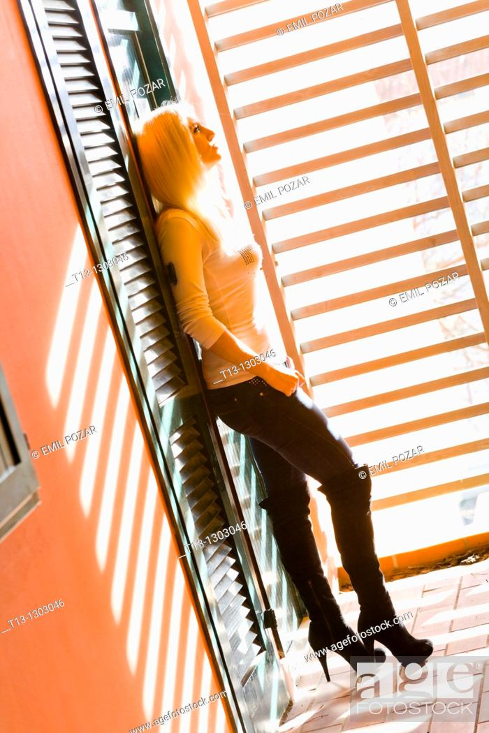 Stock Photo: Standing alone in a corridor young woman in high boots.