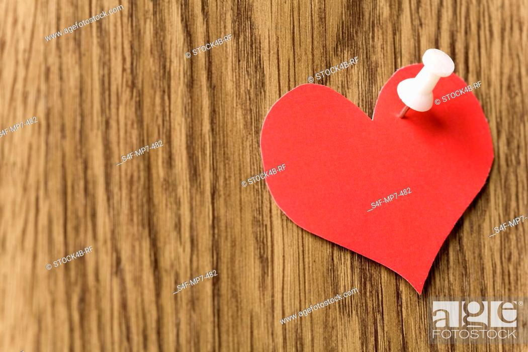 Stock Photo: Red heart with a pin.