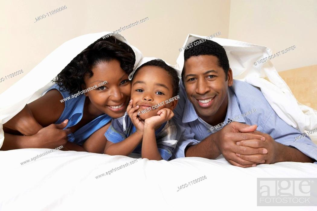 Stock Photo: Family with son 3-6 lying underneath sheet portrait.