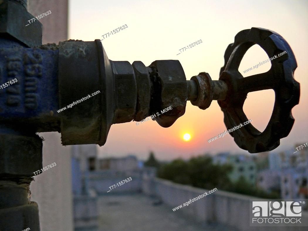 Stock Photo: A revolving cock, water pipeline going to overhead water storage on a building terrace.