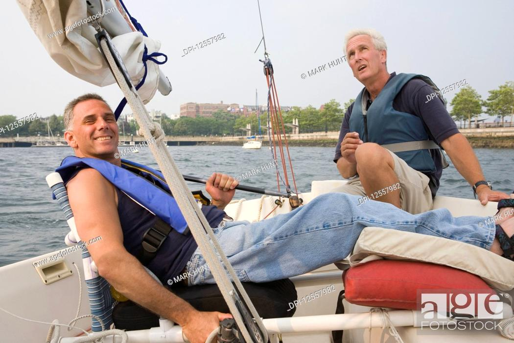 Stock Photo: Portrait of a mid adult man reclining in a boat for adaptive sailing with a middle-aged man sitting beside him.