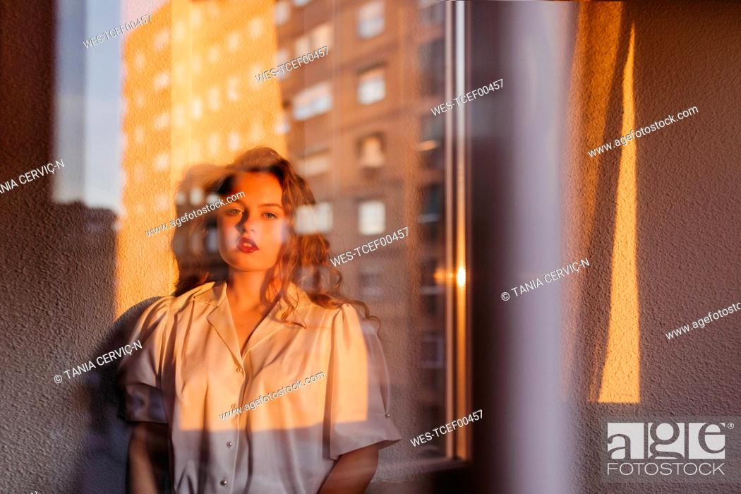 Stock Photo: Portrait of beautiful young woman behind windowpane at home.