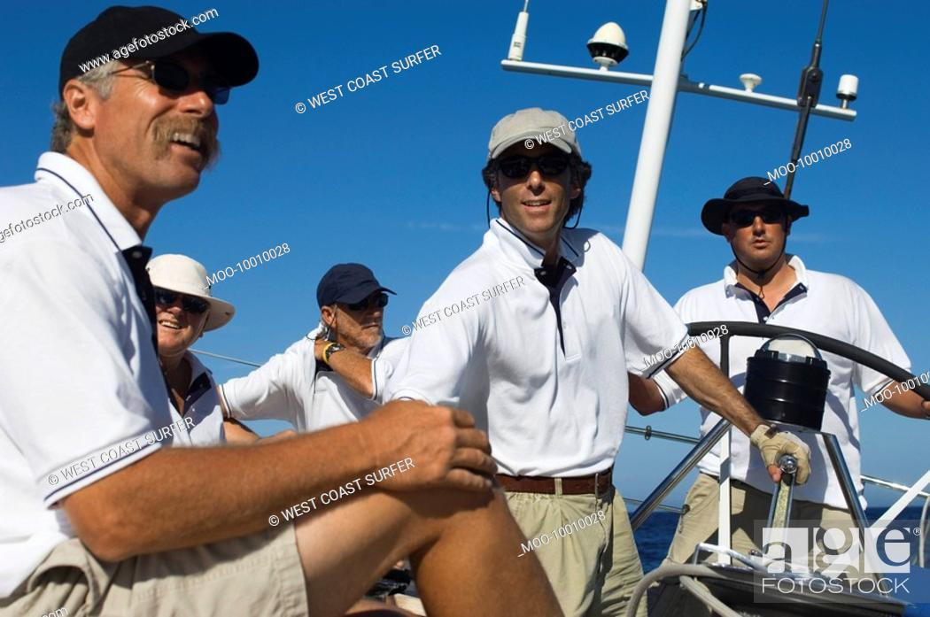 Stock Photo: Sailors relaxing on yacht by helm.