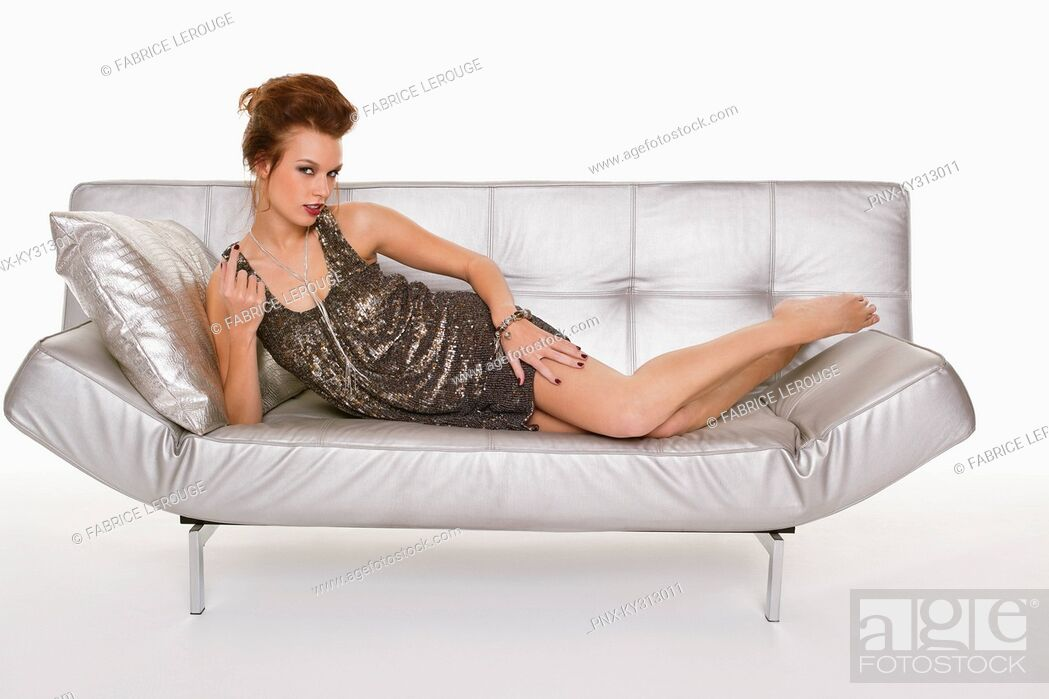 Stock Photo: Young woman in formalwear lying on sofa.