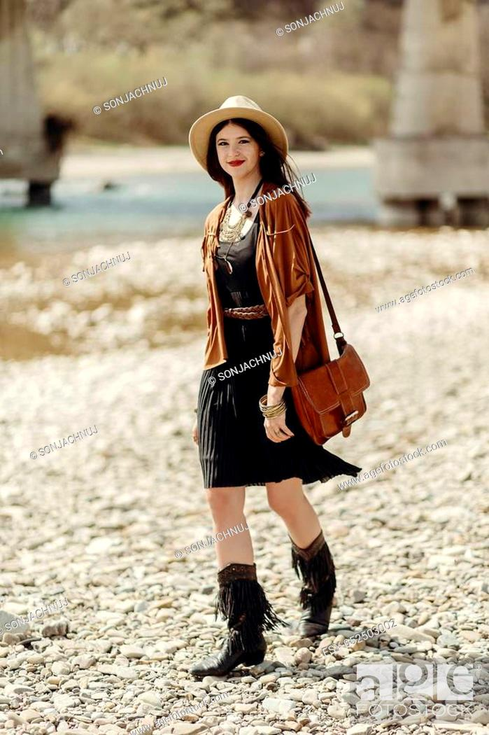 Stock Photo: stylish hipster woman in hat, fringe poncho and boots walking on river beach. boho traveler girl in gypsy look, summer travel. atmospheric moment.
