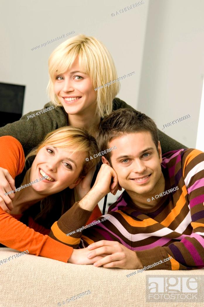 Stock Photo: Portrait of a young man smiling with two young women.