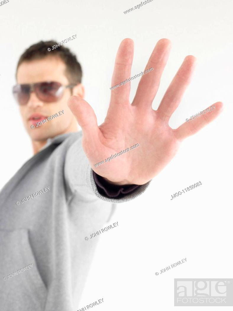Stock Photo: Man in sunglasses viewed past extended hand.