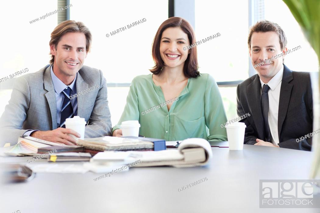 Stock Photo: Portrait of smiling business people with coffee at table.