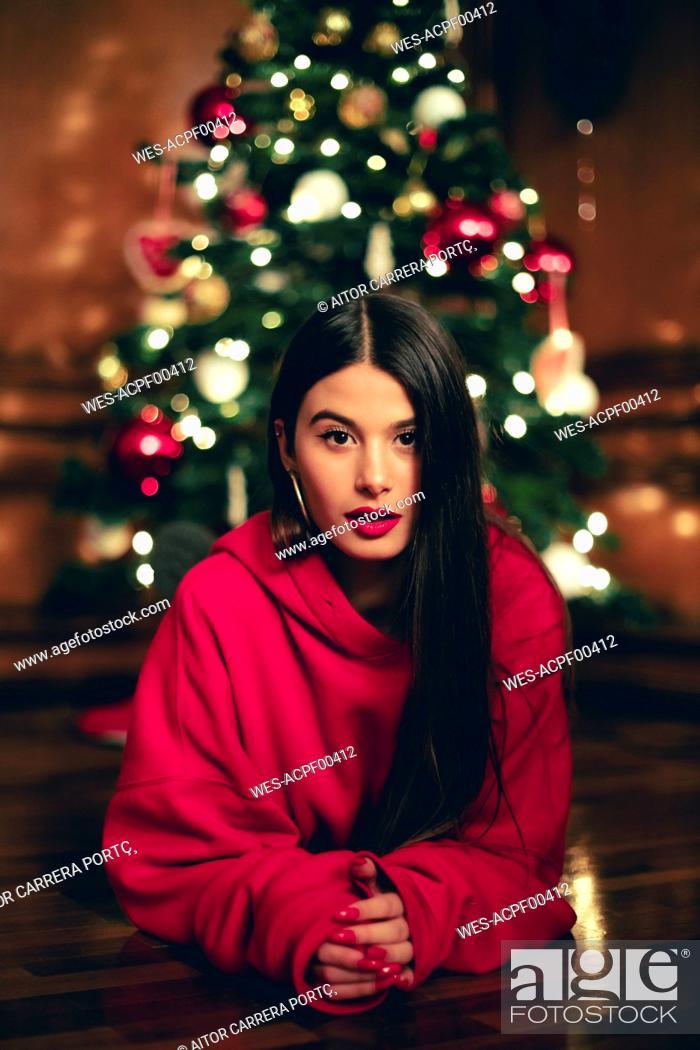 Stock Photo: Portrait of teenage girl lying on the floor in front of Christmas tree.