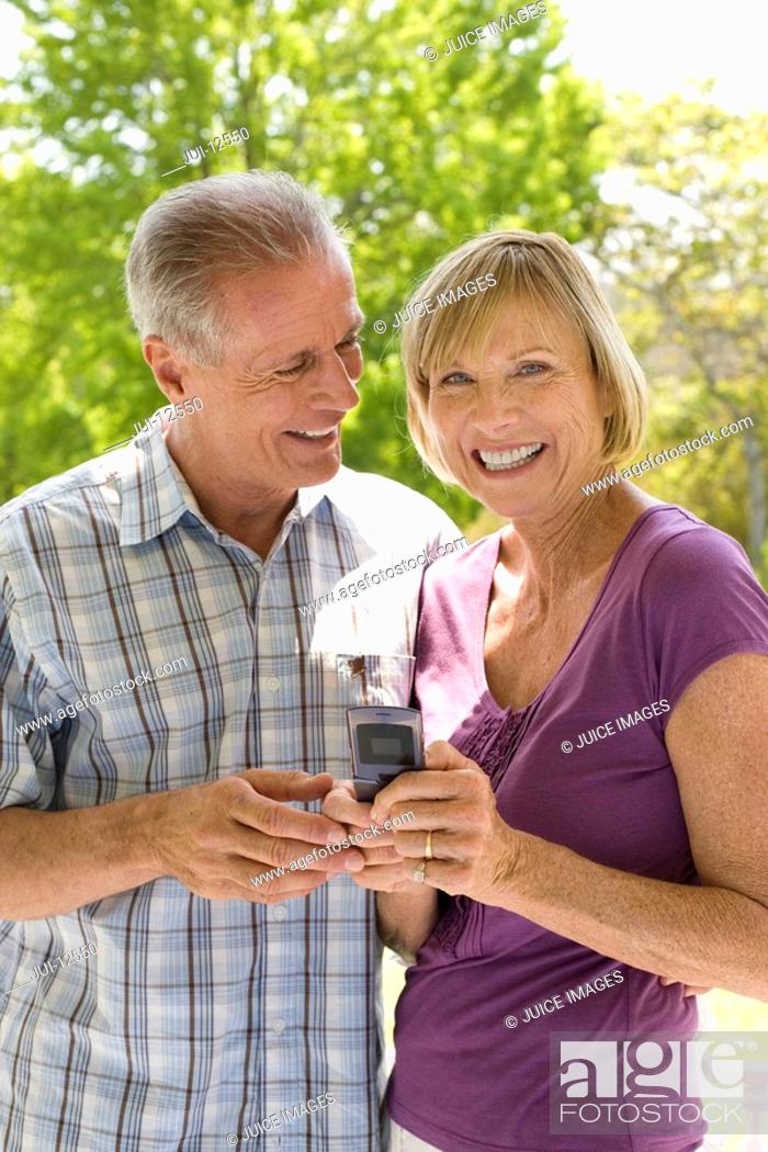 Stock Photo: Mature man smiling at woman with mobile phone outdoors, portrait of woman.