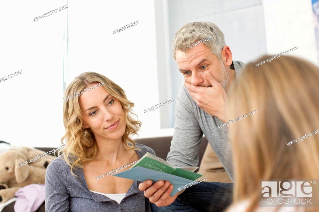 Stock Photo: Germany, Leipzig, Parents watching school report of girl.