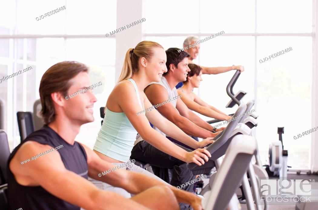 Stock Photo: People working out on exercise machines in gymnasium.