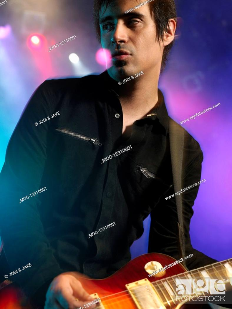 Stock Photo: Rock Guitarist on stage in Concert close up low angle view.