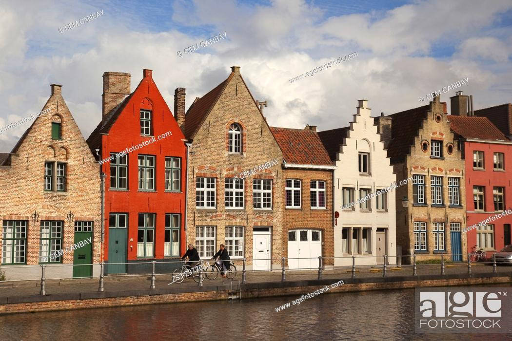 Imagen: Cyclists in front of the the colorful traditional houses by the canal in the city centre, Bruges, West Flanders, Belgium, Europe.
