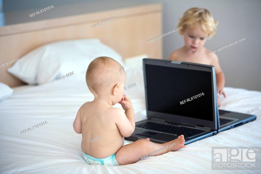 Stock Photo: Two babies 6-12 , 12-24 months playing with two laptop computers.