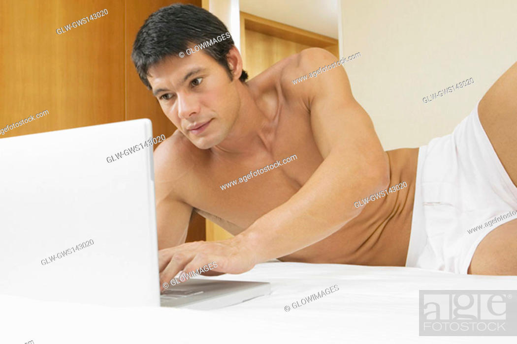 Stock Photo: Mid adult man lying on the bed and using a laptop.