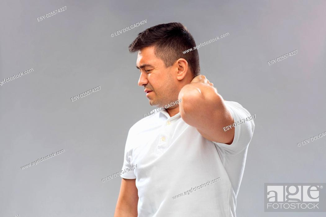 Stock Photo: people, healthcare and problem concept - unhappy man suffering from neck pain over gray background.