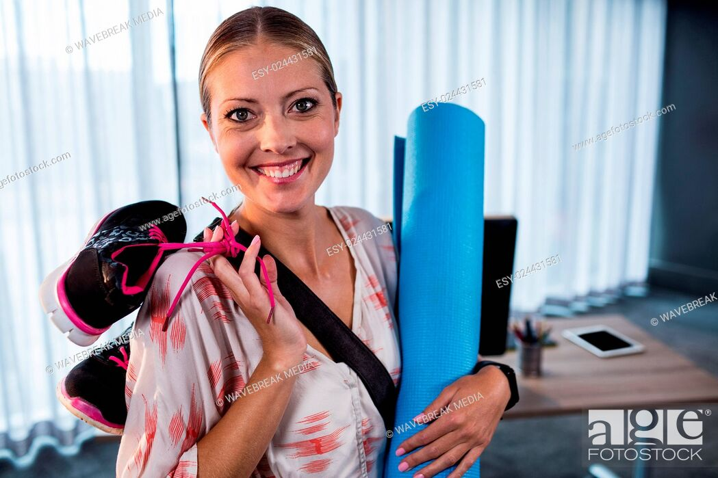Stock Photo: Casual businesswoman with yoga mat and sports shoes.