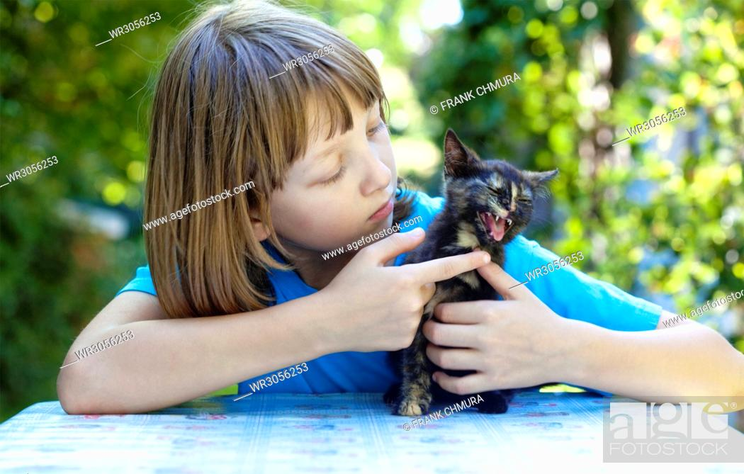 Stock Photo: Boy Playing with a Black Kitten at the Table.
