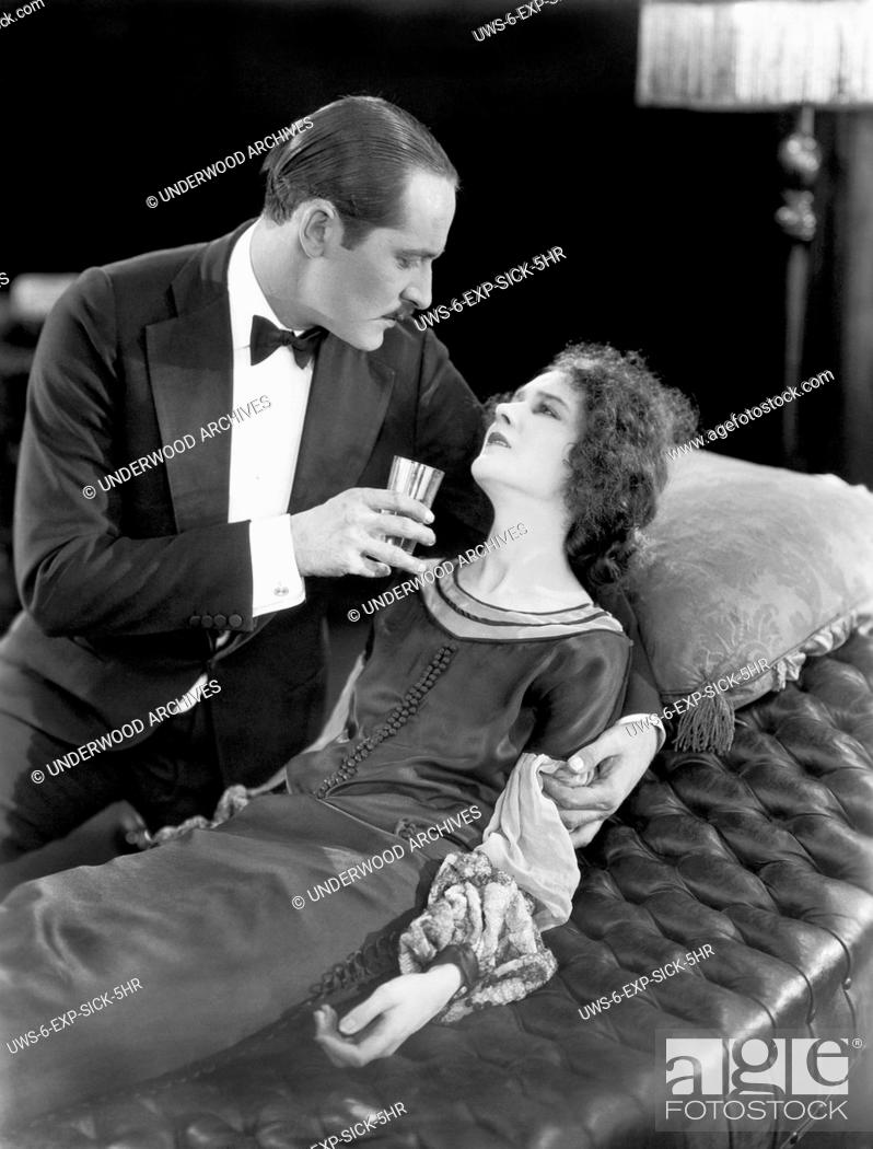 Stock Photo: Hollywood, California: 1925 A scene in the early silent movie, Fifth Avenue Models, with actor Norman Kerry tending to an ill Mary Philbin.