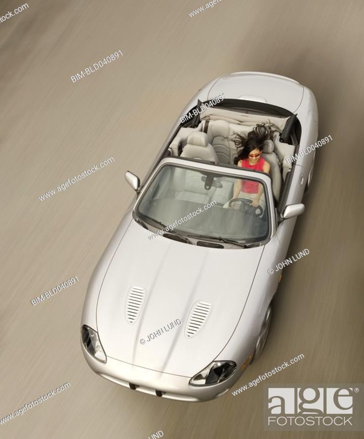 Stock Photo: Hispanic woman driving convertible car.