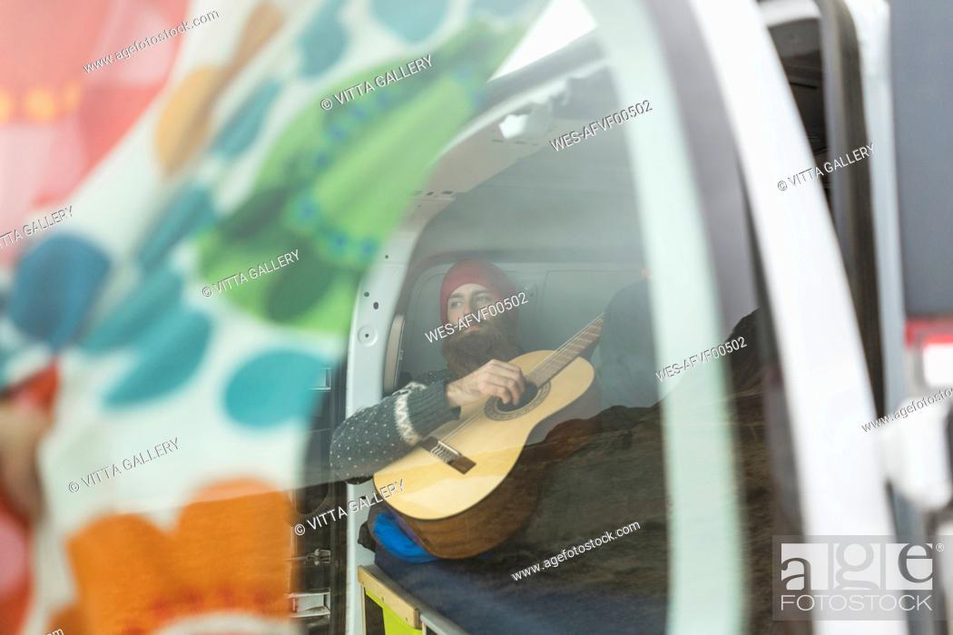 Imagen: Man lying in van playing guitar.