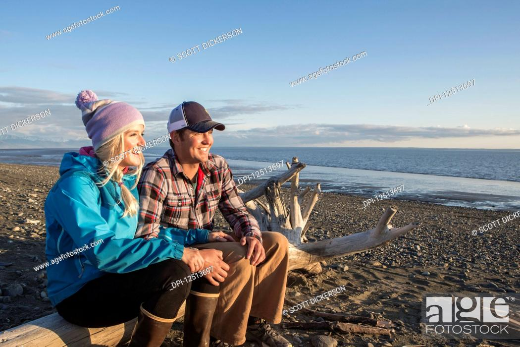 Imagen: A young couple sits on a piece of driftwood on a beach looking out to the ocean at sunset; Anchorage, Alaska, United States of America.