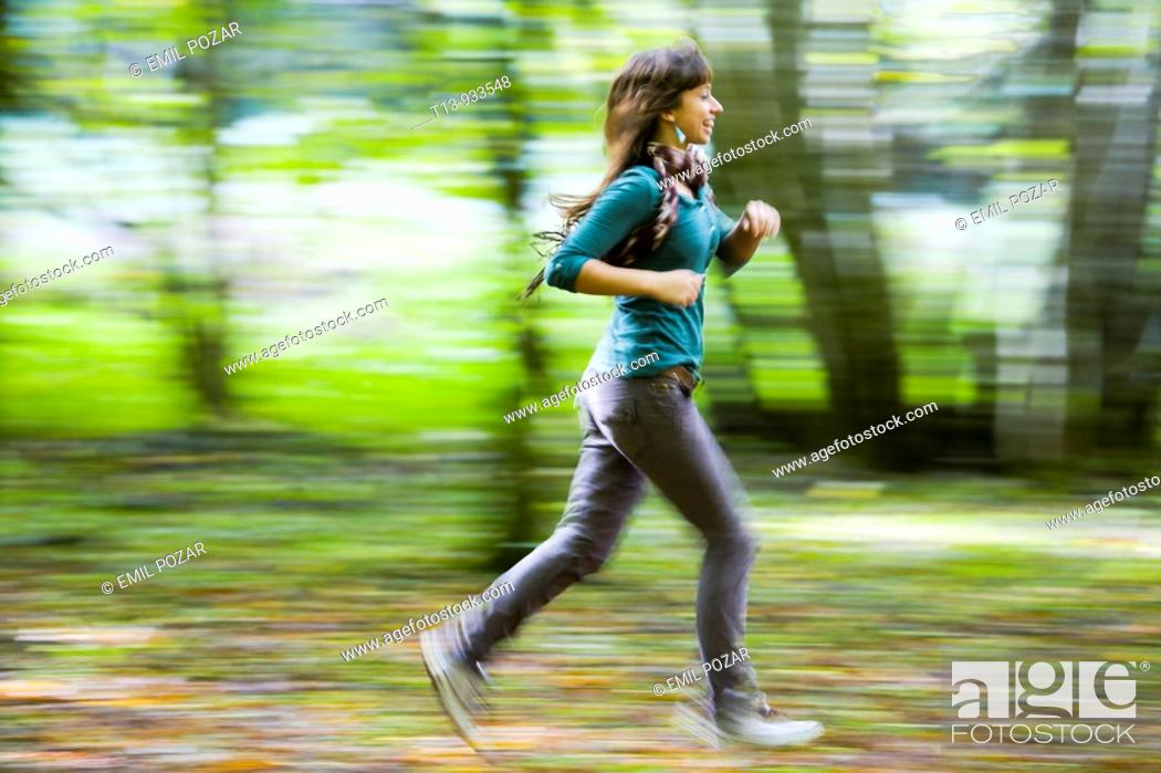 Stock Photo: Running young woman in forest, panning photo.