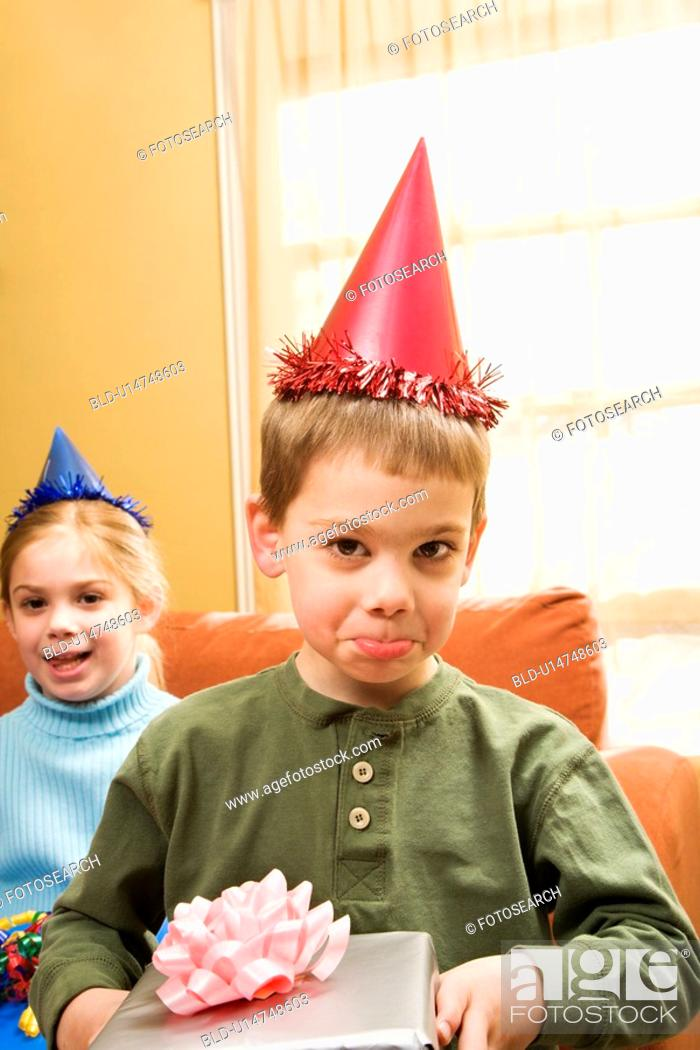 Stock Photo: Caucasian boy wearing party hat pouting and looking at viewer.