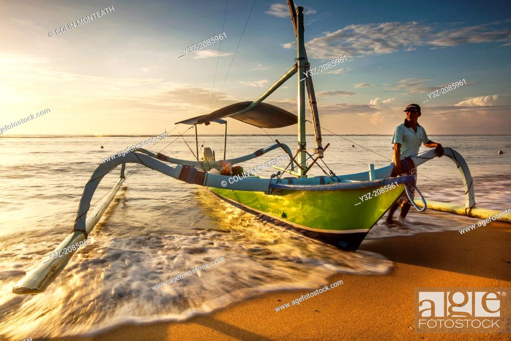 Stock Photo: Fishing vessel with outriggers on beach at dawn, Sanur, Bali, Indonesia.