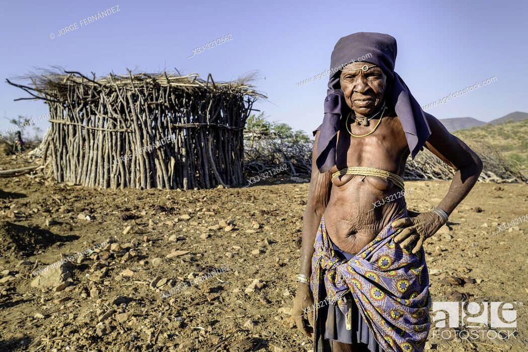 Stock Photo: portrait of an old Mucubale woman with traditional brass in front of her hut.