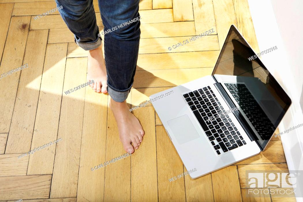 Stock Photo: Germany, Berlin, Young woman feets walking by laptop.