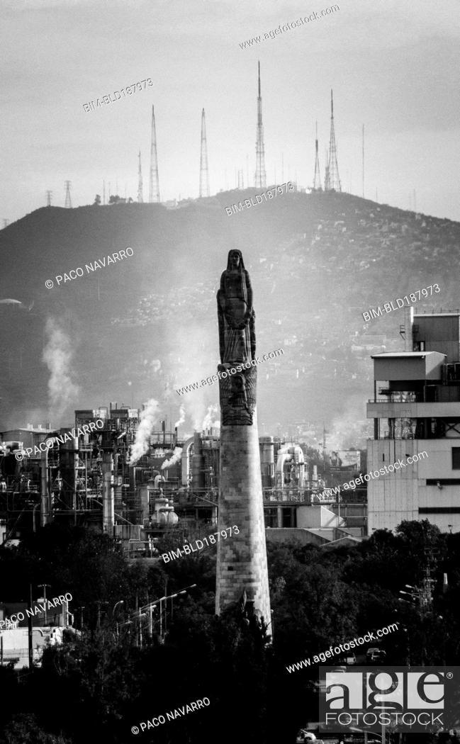 Stock Photo: Statue on pillar in cityscape.