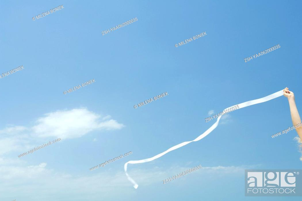 Stock Photo: Woman holding up streamer against blue sky, cropped view.