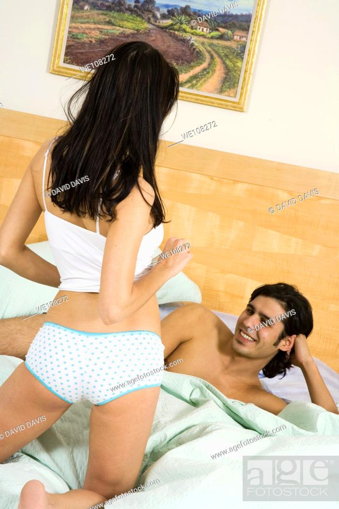 Stock Photo: Romantic couple engaged in a playfull striptease.