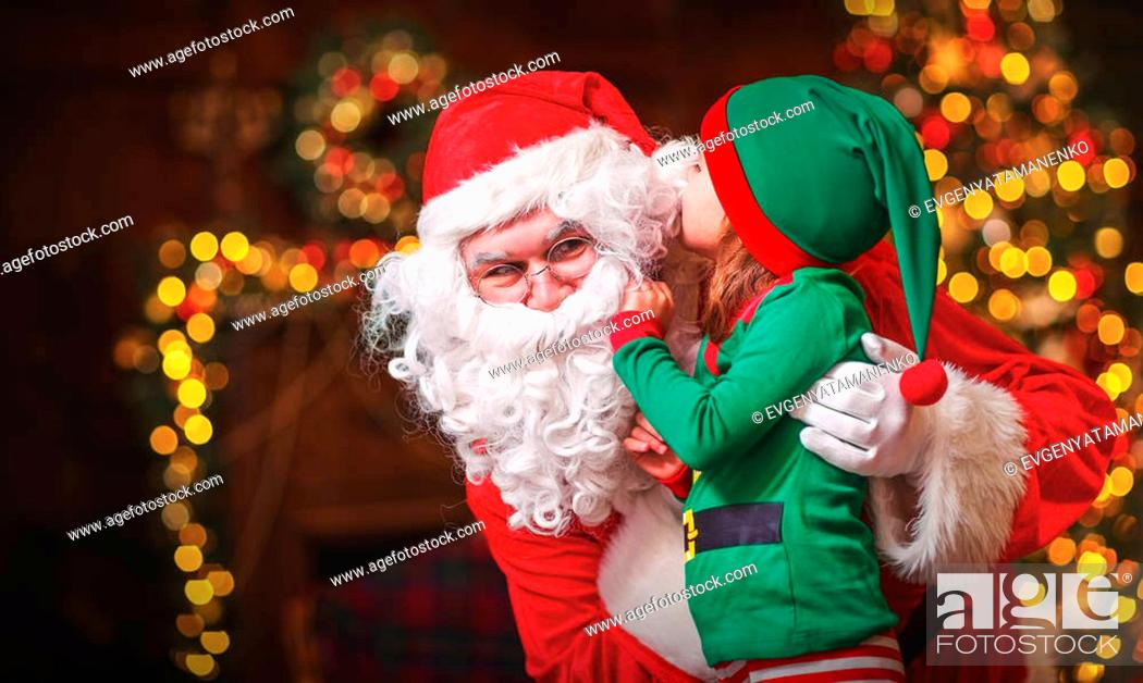 Imagen: happy cheerful child elf helper in the hands of Santa Claus at Christmas.