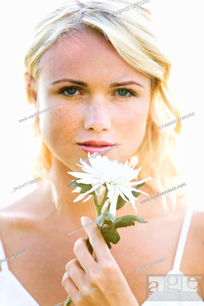 Stock Photo: Portrait of a young woman holding a white flower.