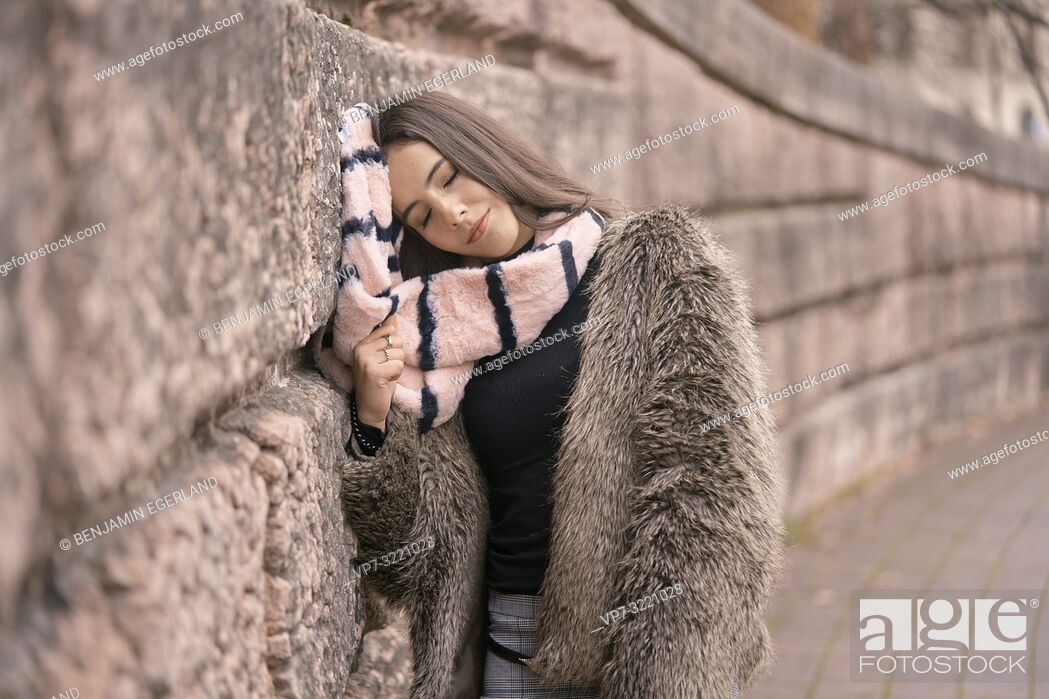 Stock Photo: sleepy woman resting head on scarf and stone wall, in Munich, Germany.