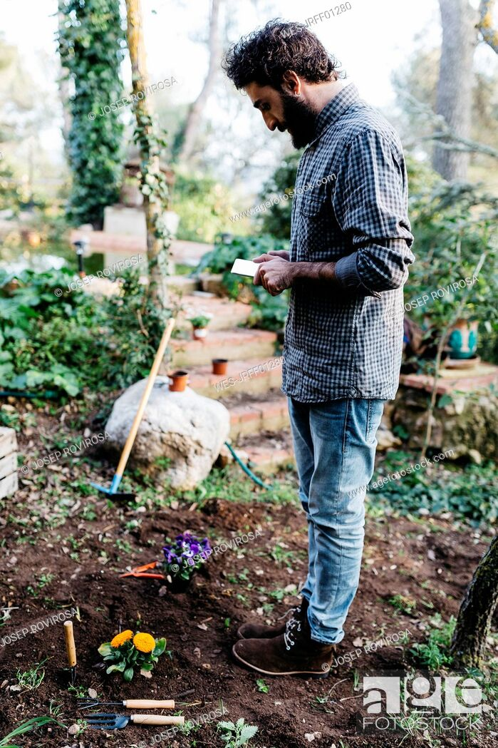 Imagen: Man taking photographs with a tablet of flowers planted in garden.