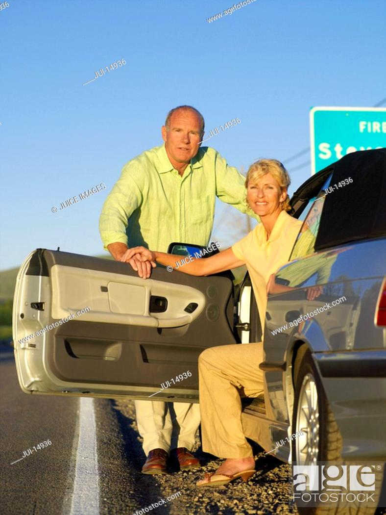 Stock Photo: Mature couple getting out of car on roadside, portrait.