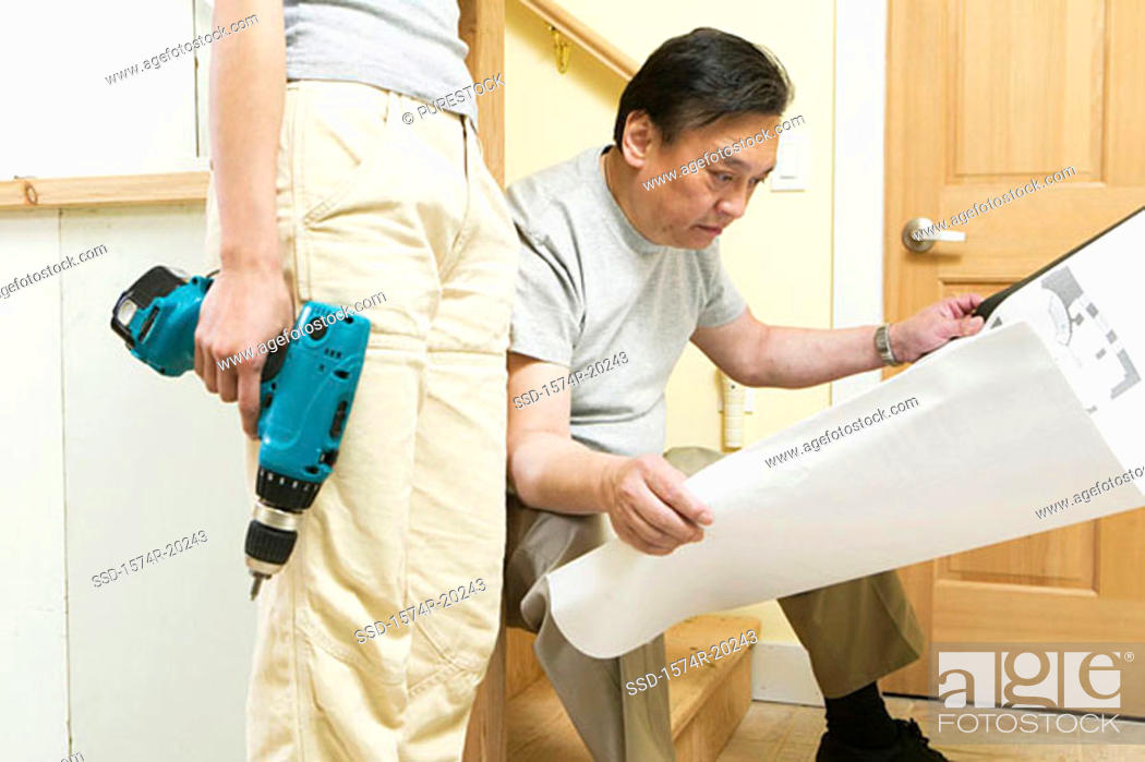 Stock Photo: Mid section view of a young woman holding a drill with a mid adult man looking at a blueprint.
