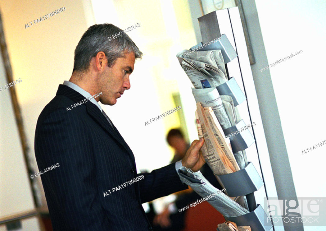 Stock Photo: Businessman looking at newspapers on wall rack.