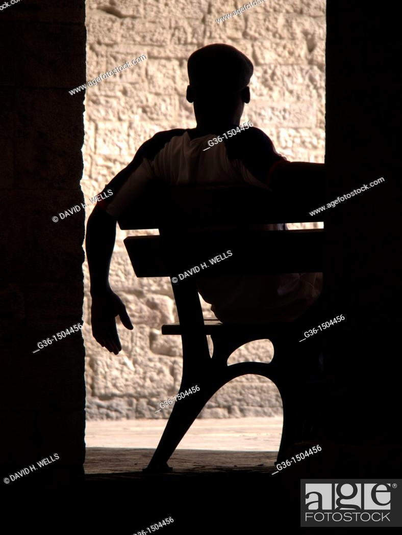 Stock Photo: Man sits on bench in Todi, Perugia, Italy.